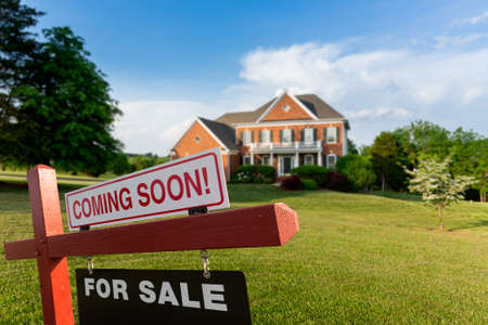 single family: For Sale and Coming Soon  sign in front of large brick single family house in expansive grass yard for real estate opportunity
