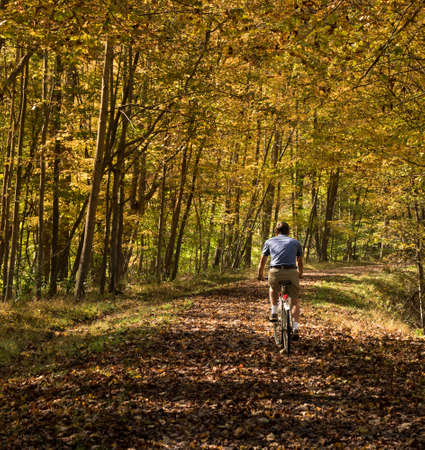 west virginia: Senior adult caucasian man cycling away down a leaf covered Deckers Creek Rail trail near Morgantown in West Virginia Stock Photo