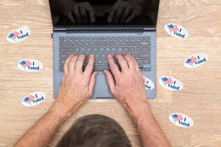 i voted: Multiple I Voted stickers with USA flag on desk of computer hacker illustrating potential voter fraud with illegal votes and need for recount