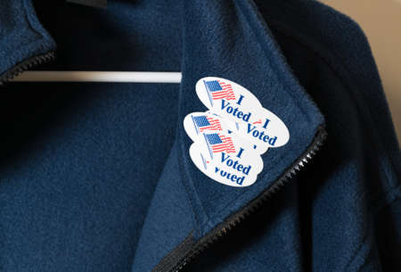 voted: Multiple I Voted stickers with USA flag on blue jacket on hanger illustrating potential voter fraud with illegal votes and need for recount Stock Photo
