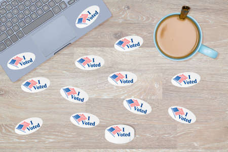 voted: Multiple I Voted stickers with USA flag on desk of computer hacker illustrating potential voter fraud with illegal votes and need for recount