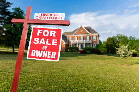 For Sale and Under Contract realtor sign in front of large brick single family house in expansive grass yard for real estate opportunity