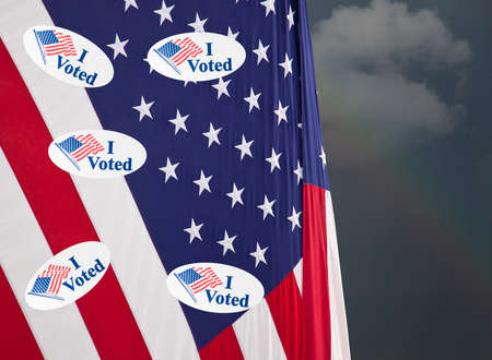 Multiple I Voted stickers with USA flag on stormy background illustrating potential voter fraud with illegal votes and need for recount Stock Photo