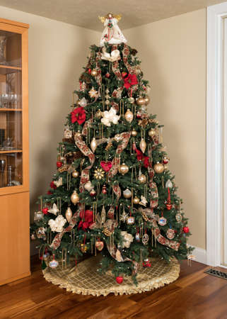 ornately: Ornately decorated christmas tree in the corner of a modern living room with cover under the branches