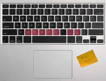 above 18: Laptop computer keyboard spelling out April 18 2017 as Tax Day Stock Photo