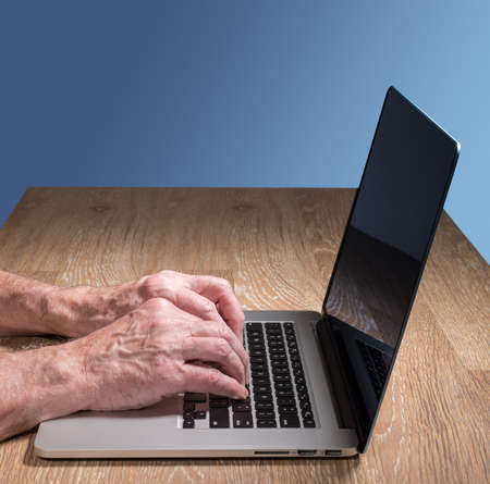 senior adult man: Senior caucasian adult man types on modern keyboard of laptop or ultrabook on wooden desk with copy space