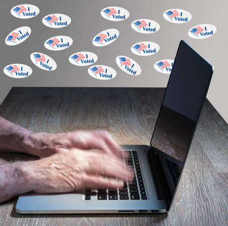 i voted: Multiple I Voted stickers with USA flag on wall above desk of computer hacker illustrating potential voter fraud with illegal votes and need for recount Stock Photo
