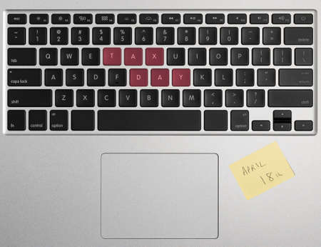 above 18: Laptop computer keyboard spelling out April 18 2017 as Tax Day with yellow sticky note as a reminder