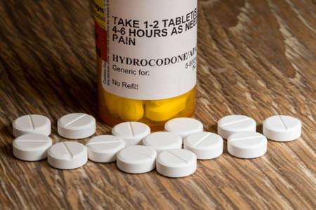 sobredosis: Foto cercana de la botella de prescripción para tabletas y pastillas de hidrocodona en la mesa de madera para la ilustración de la epidemia de opiáceos