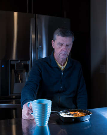 alimentos congelados: Lonely and depressed senior male sitting alone at kitchen table eating a microwaved ready meal of curry and mug of tea or coffee