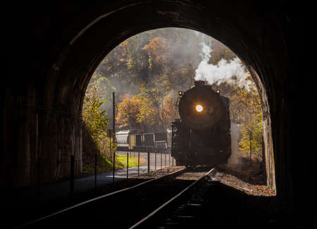 powerful: Old steam train pulling into a tunnel belching steam and smoke