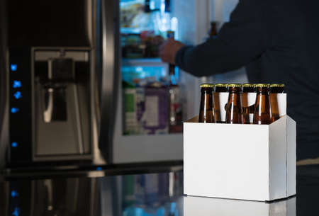 six pack: Six pack of brown beer bottles in plain white cardboard carrier with copy space on stainless steel kitchen or bar counter. Open fridge or refrigerator out of focus in rear.