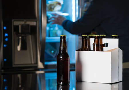 6 pack beer: Six pack of brown beer bottles in plain white cardboard carrier with copy space on stainless steel kitchen or bar counter. Open fridge or refrigerator out of focus in rear.