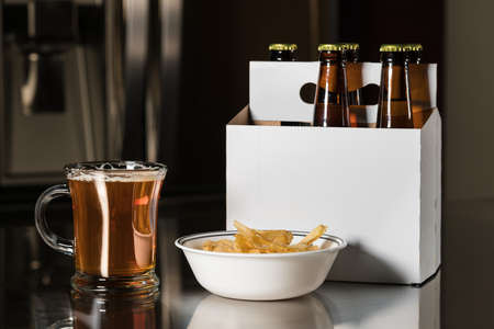 6 pack beer: Six pack of brown beer bottles in plain white cardboard carrier on stainless steel kitchen or bar counter with poured ale in tankard