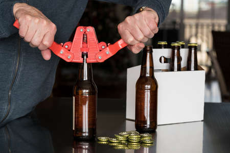 Brewer of home brewed beer using a red bottle capper to attach the metal cap to the top of the glass bottle with a six pack in background.