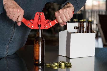가정의 맥주 양조자는 빨간 병 뚜껑을 사용하여 맥주를 양조하여 배경에 6 개 팩으로 유리 병 상단에 금속 캡을 부착했습니다. 스톡 콘텐츠