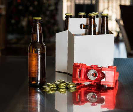 가정에서 양조 한 맥주는 유리 병 꼭대기에 금속 캡을 붙이기 위해 붉은 병 뚜껑을 사용합니다. 배경에는 6 팩 스톡 콘텐츠