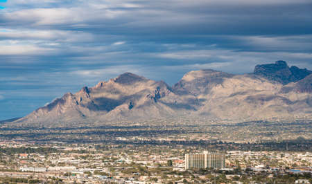 Downtown area of Tucson in Arizona with the sun lighting the buildings while storm clouds gather over distant Santa Catalina mountain range
