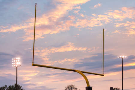post: Yellow american football goal posts at school field against the lights and clouds of setting sun