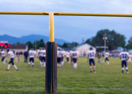uprights: Yellow american football goal posts at school field with the student athletes on the field