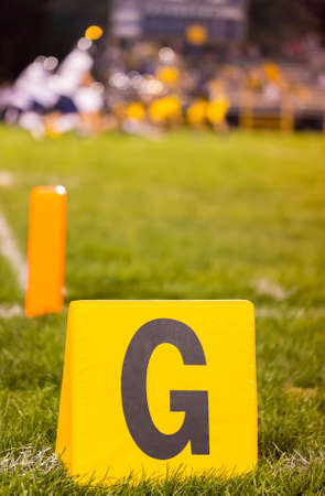 uprights: Yellow american football goal line marker at school field with the student athletes on the field