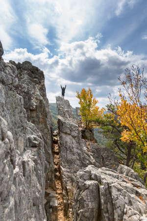 Junger Bergsteiger erreicht den Gipfel des felsigen Granitbergs von Seneca Rocks in West Virginia