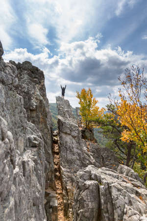 seneca: Young climber reaches the summit of the rocky granite mountain top of Seneca Rocks in West Virginia Stock Photo