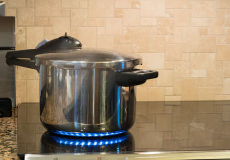 stockpot: Stainless steel pressure cooker letting off steam on a modern induction cooking hob with glass top