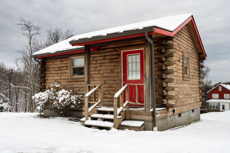 Small log cabin on snowy winter day with steps leading up to red painted door.