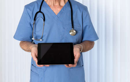 Senior male caucasian doctor with stethoscope in medical scrubs looking up and holding electronic tablet for message Reklamní fotografie