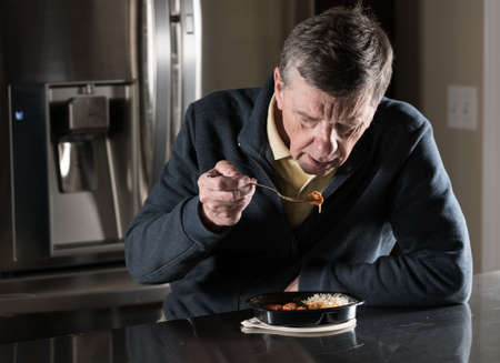 eating dinner: Lonely and depressed senior male sitting alone at kitchen table eating a microwaved ready meal of curry from plastic tray