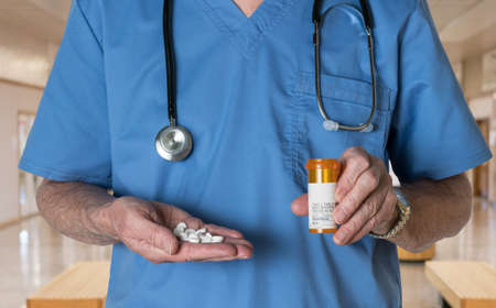 opioid: Senior male doctor with stethoscope in medical scrubs and holding bottle and tablets of generic white RX tablets to illustrate opioid epidemic