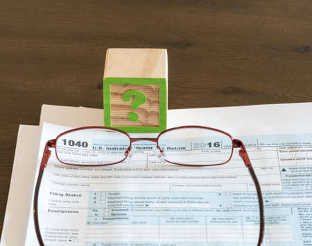 finance problems: Question mark wooden block illustrating problems or issues in completing US IRS tax form Stock Photo
