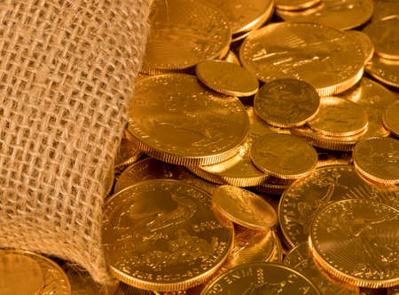 suggesting: Gold Eagle one ounce coins being poured out of a woven sacking bag suggesting immense wealth Stock Photo