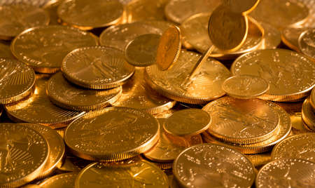 suggesting: Gold Eagle one ounce coins being poured down onto a pile of other golden money suggesting immense wealth
