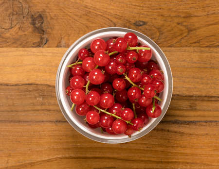 Aerial or top view of a white glass bowl of organic redcurrant or red currant fruit  sitting on old wood table surface Stock Photo
