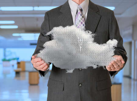 Senior male caucasian executive holding cloud computing shape. Connection to electronic records via WiFi to web services applications Stock Photo