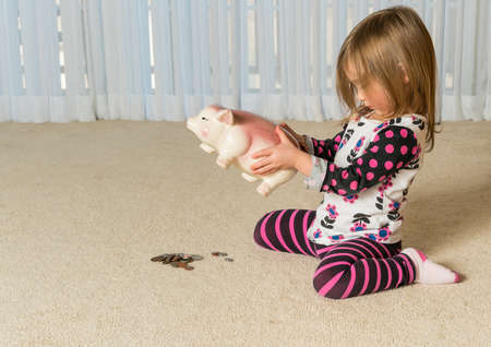 pay money: Young girl on floor of home trying to get money to pay off debt  out of a piggy bank for expenses in the future Stock Photo
