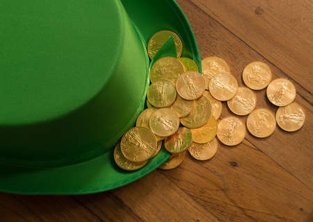 Treasure of pure gold coins inside a green velvet hat on wooden table to celebrate luck on St Patricks Day of March 17th Stock Photo
