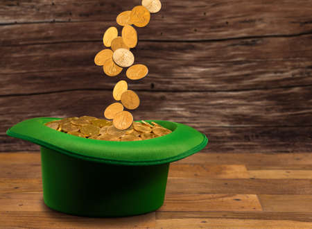 Treasure of pure gold coins pouring down onto a green velvet hat on wooden table. Concept image to celebrate luck on St Patricks Day of March 17th