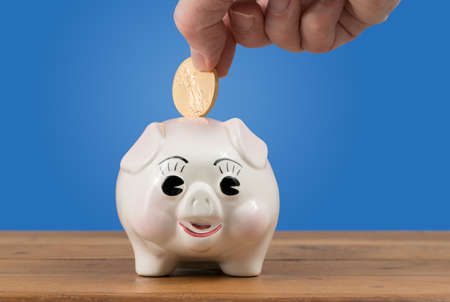 Pottery piggy bank on a table or shelf with a hand inserting a gold coin for savings or investment in the future