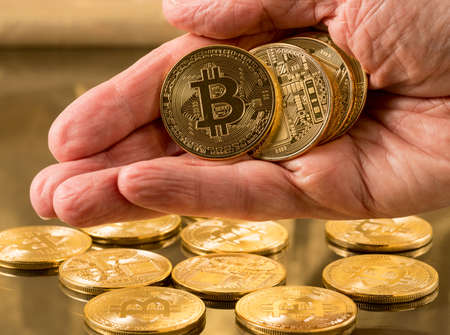 electronic commerce: Stack of bit coins or bitcoin held in mans hand on gold background to illustrate blockchain and cyber currency