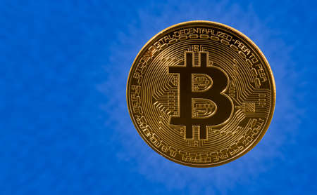 decentralized: Single bit coin or bitcoin on blue cloud background to illustrate blockchain and cyber currency
