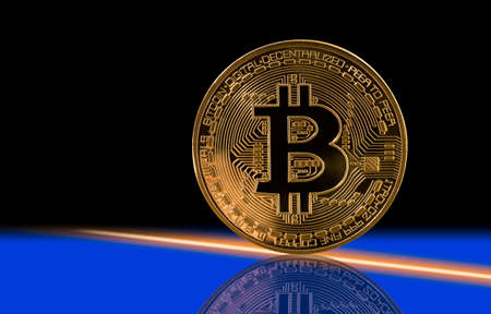Single bit coin or bitcoin with reflection on black and blue background to illustrate blockchain and cyber currency