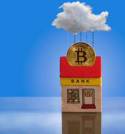 roof windows: Toy brick bank building with bitcoins inside the windows and one coin emerging from roof into cyberspace. Illustration of the importance of modern techology to banking Stock Photo