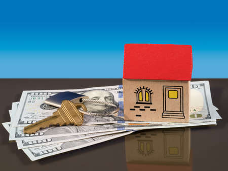 implied: Toy wooden home on US 100 dollar bills with a door key and lock to illustrate house purchase or rental. Mortgage payments to a bank are implied. Stock Photo
