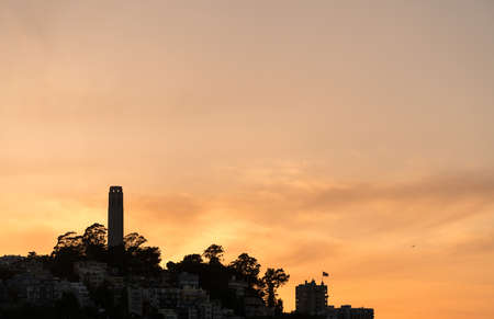 residential structure: Skyline of the Coit Tower and residential area of San Francisco in California. Sihouette of the construction and the homes against the orange sky of sunset