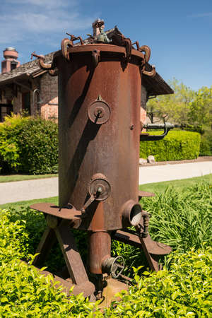 Rusty iron wine grape press in garden in Yountville, Napa Valley in California