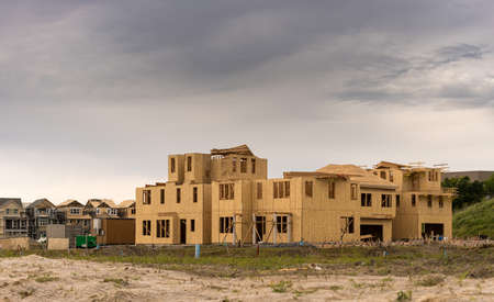 rafters: Wooden sheathing on exterior of new townhouses and single family homes in California with dark clouds to suggest recession
