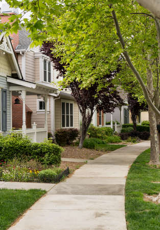 Single family homes along concrete footpath in California tree lined residential sub division Stock Photo